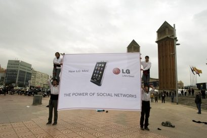 Two people stand on the shoulders of two others to display a LG Mini promotional banner next to the Venetian Towers at Plaza España, Barcelona.