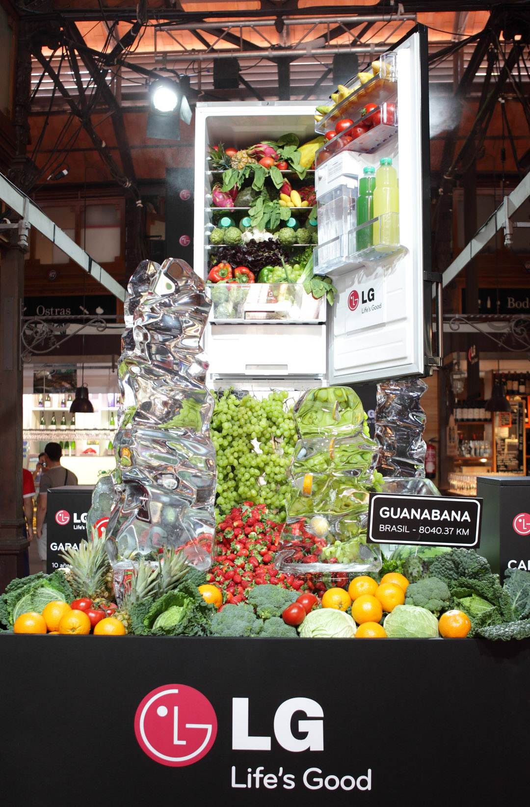 A giant-sized LG refrigerator display in…, with healthy fruits, vegetables and juices flowing from the appliance's interior like a waterfall.