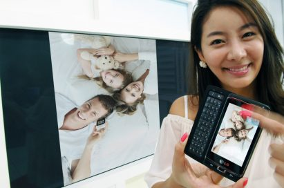 A female model is showing a family photograph on the TV by using LG's unique multimedia sharing technology on her LG Optimus 7
