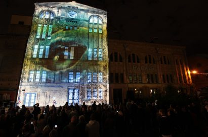 A clear image of an animal's eye is projected onto the façade in Kulturbrauerei while spectators watch on in amazement.