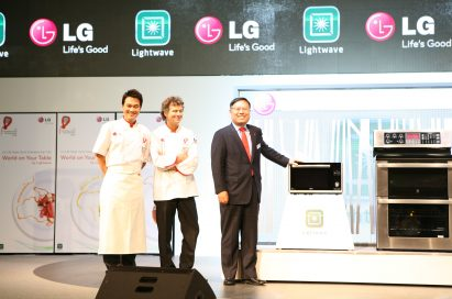 Two chefs and one LG executive pose at the front of the stage with the LG microwave and cooking oven