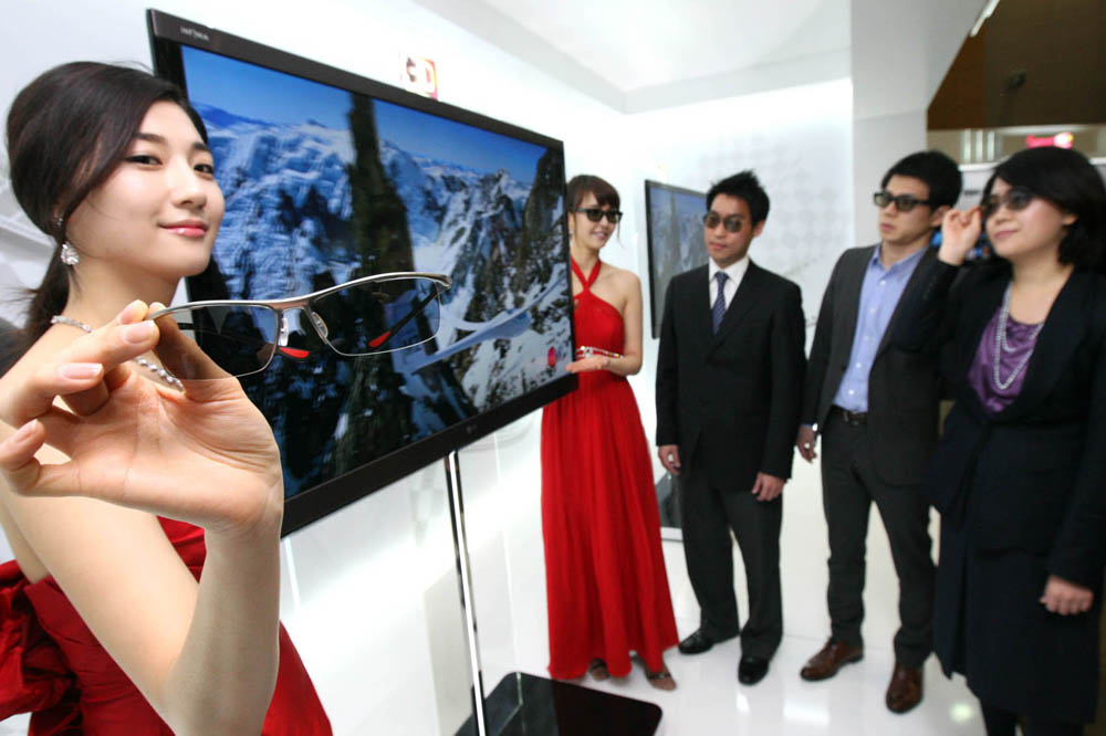 Another view of LG's NEW CINEMA 3D TV with models standing next to it and people looking at it wearing 3D glasses