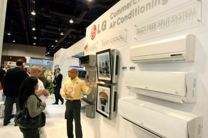 A man explains LG's Duct Free Split System commercial air conditioners to visitors of the company's booth.