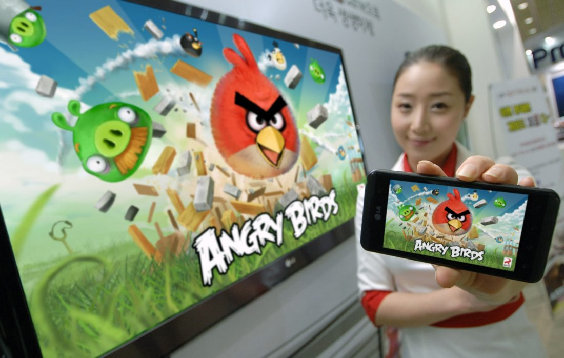 A model holding an OPTIMUS SERIES SMARTPHONE with ANGRY BIRDS RIO on the screen