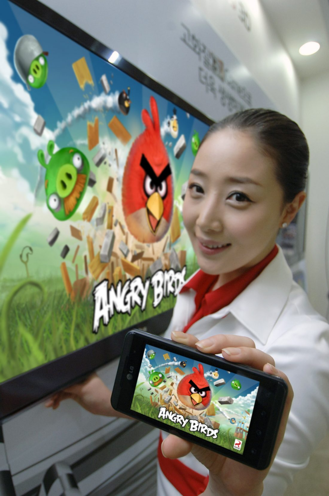 A close view of a model holding an OPTIMUS SERIES SMARTPHONE with ANGRY BIRDS RIO on the screen