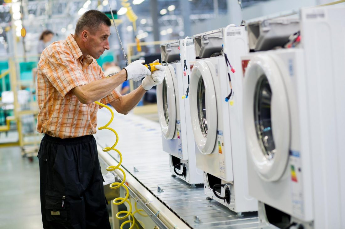 A staff member assembles washing machines on appliance production lines in Poland