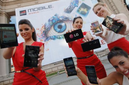 Four female models hold eight LG LTE smartphones in front of a huge MWC logo banner outside the event venue of MWC 2012.