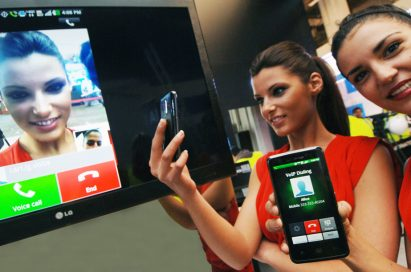 Two models try out the Voice to Video Convention feature on their LG mobile phones.