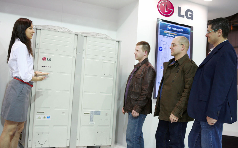 A female attendant explains LG's Multi V HVAC solution to three men at MCE 2012.