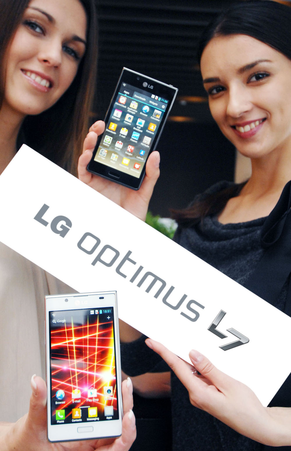 Another image of two female models holding the LG OPTIMUS L7 smartphone and its brand name panel at the launch event