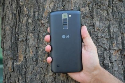LG K7 smartphone with user's hand visible, held in front of tree
