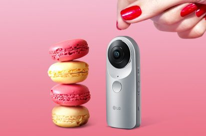 LG 360 CAM positioned next to a stack of macaroons with a woman's hand visible above