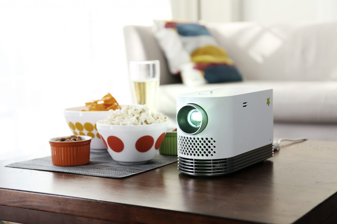 Front view of the LG Probeam Laser Projector (model HF80J) facing 15 degrees to the left on a table with snacks in bowls