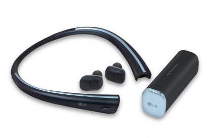 The front left view of the LG Tone Free with the wireless earbuds extracted from the neckband and the optional charging cradle on the right