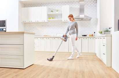A woman vacuums a kitchen floor with the LG CordZero Handstick