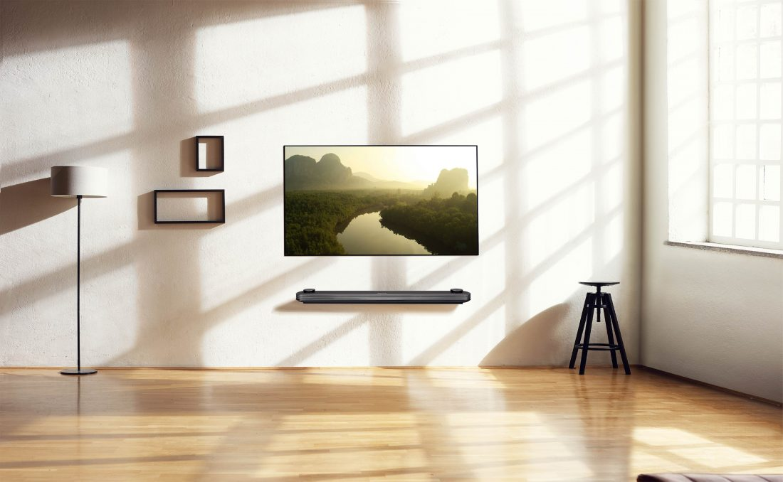 An LG SIGNATURE OLED TV W is on the wall of an apartment with some interior décors while displaying a nature scene on its screen.