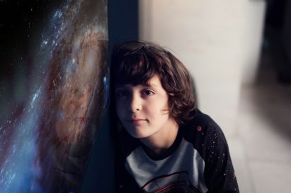 A small boy leans against the screen of the LG SIGNATURE OLED TV W, there is a picture of a galaxy on the screen.