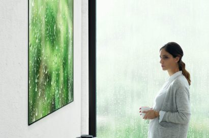 Another view of a woman standing looking at the LG SIGNATURE OLED TV W (model W7)