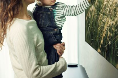 Another view of a mother and small child look at an LG SIGNATURE OLED TV W and the child is touching the screen