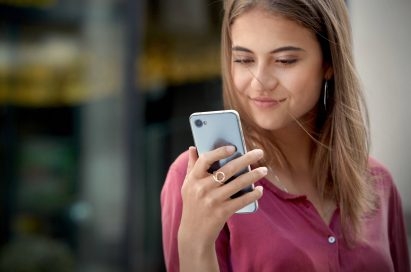 A woman looking at the LG G6 in her hand