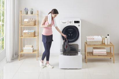 A woman in athletic wear putting gym shorts in the LG TWINWash™ Mini unit of the TWINWash™ washing machine in a laundry room