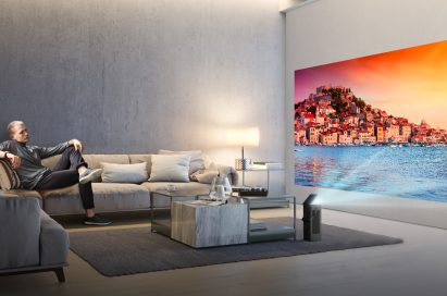 A man seated on a couch watches video projected onto a wall from LG's HU80K series 4K UHD projector