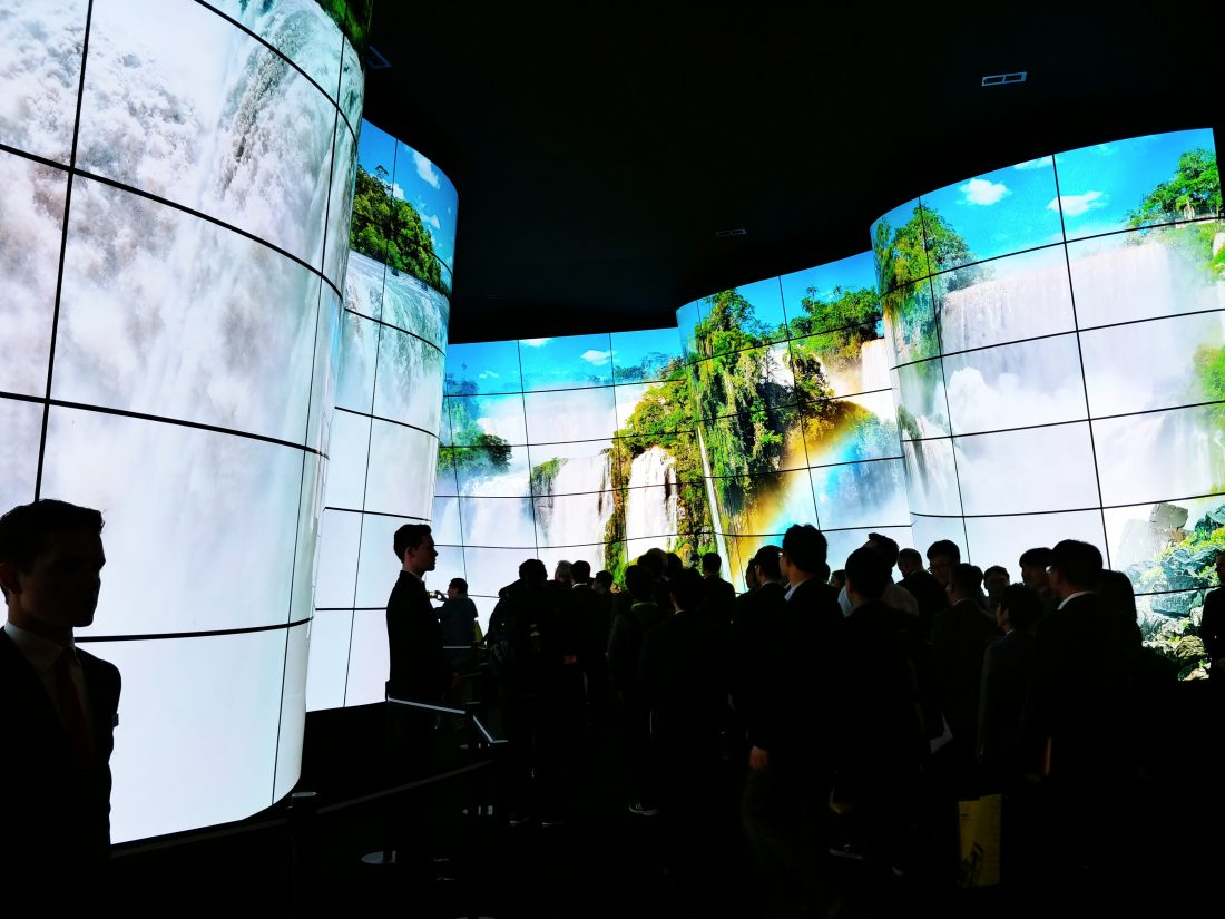 People standing before the entrance of the LG OLED Canyon, which displays a huge waterfall