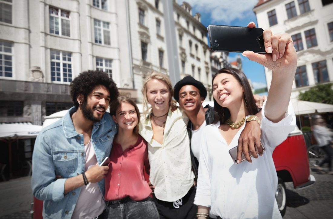 A group of friends uses the LG Q6 phone to take a selfie