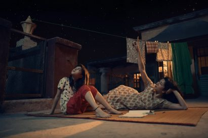 "A screenshot of LG India's ""Astronaut"" video, there are two women looking up towards the night sky"