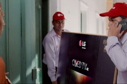 "A screenshot of LG India's ""Astronaut"" video, two men are delivering LG OLED TV to a woman's house."