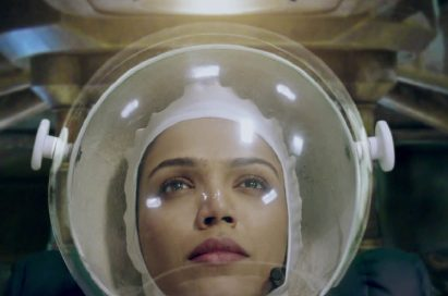 "A screenshot of LG India's ""Astronaut"" video, a woman wearing the astronaut suit is waiting for the departure of the spaceship."