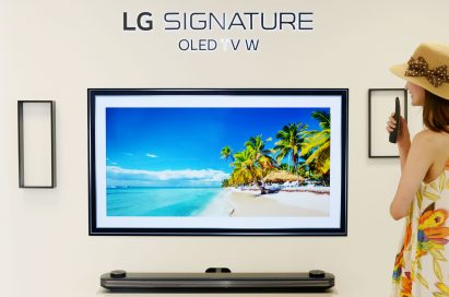 A woman looks at LG SIGNATURE OLED TV W which displays the tropical beach and coconut trees on its screen.