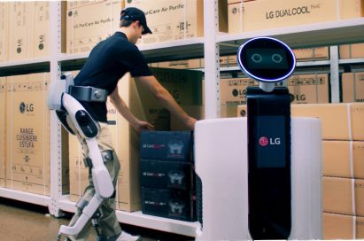 Man wearing LG CLOi SuitBot to move a box to the LG Shopping Cart Robot in a LG warehouse