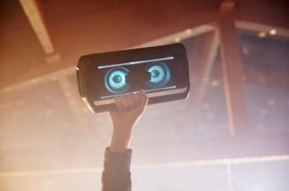 A person holds the LG XBOOM up high with ease