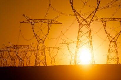 Huge metal power poles and thick wires that transfer the high-voltage electricity in front of the sunset glow