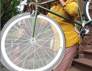 A still image of a six-second GIF image, a man walking down the porch stairs putting a bike on his shoulder