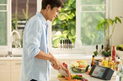 Man slicing vegetables as he looks at a recipe on the LG XBOOM AI ThinQ™ WK9 Smart Display