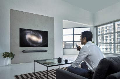 A man watching his LG OLED TV with a remote in one hand at his home