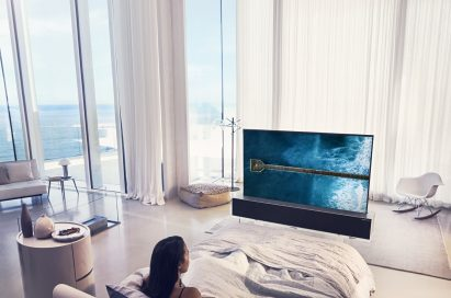 A woman enjoying watching her LG OLED TV R in its Full View mode positioned at the end of her bed