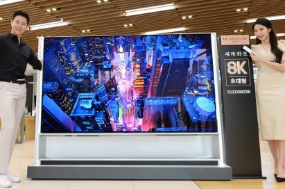 Two models demonstrating LG 8K OLED TV displaying skyscrapers