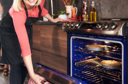 A lady in red shirts opens the door of the LG ProBake Convection® with the casserole inside the oven.