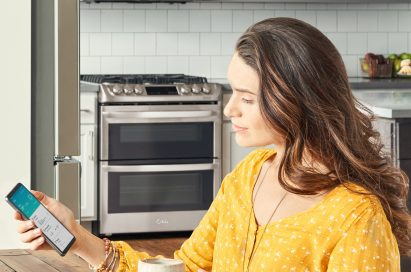 Woman sitting in her kitchen looking at a phone displaying the ThinQ™ app screen showing the device status of the washer, refrigerator and range