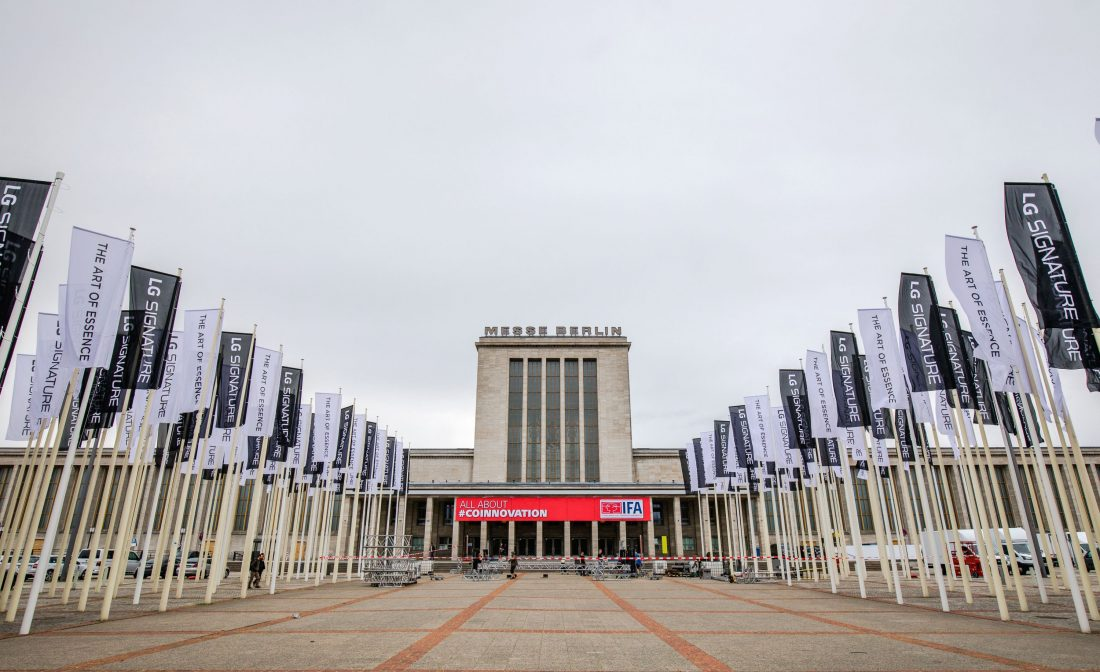 "Front view of Messegelände Berlin ExpoCenter City with promotional flags of the LG SIGNATURE brand and its brand theme ""The Art of Essence"" flying in front"