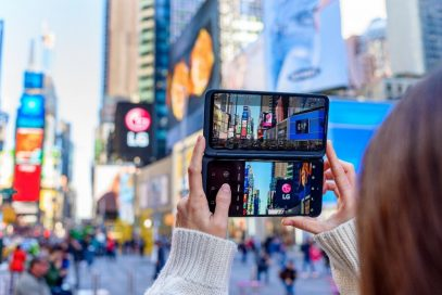 A woman holds LG G8XThinQ with LG Dual Screen in her two hands vertically to check the weather on the screen at an urban space with buildings.