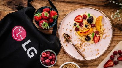 A promotional image showing an LG bag surrounded by plates and bowls of healthy natural foods including strawberries and raspberries.