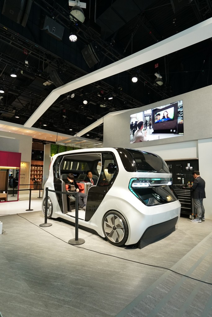 A front side view of LG's Connected Car concept with two people sitting inside, which was unveiled at CES 2020 to highlight the future of cars via LG ThinQ