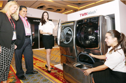 Two female employees demonstrate the large capacity of the main washer and the handy hidden SideKick compartment of the LG TwinWash washing machine to two attendees