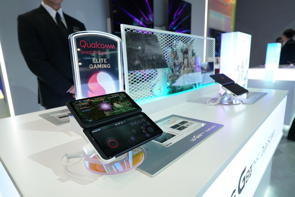 A close-up of two LG G8X smartphones strapped into LG Dual Screen on display in front of a Qualcomm Snapdragon Elite Gaming sign at CES 2020