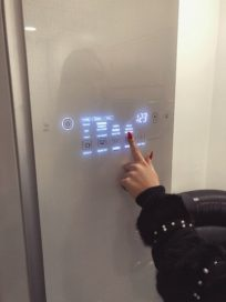 A woman pushes a button on the front door display panel of the LG Styler to set it to cleaning mode