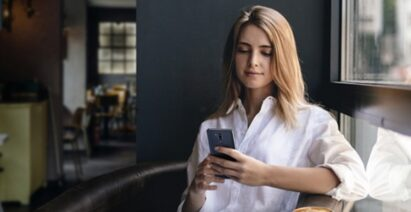 A woman uses her LG smartphone in the home